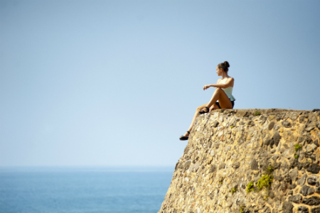 Girl siting and looking out over a body of water