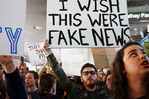 Man holding fake news sign