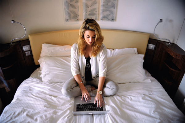 Woman taking online course on laptop in bed