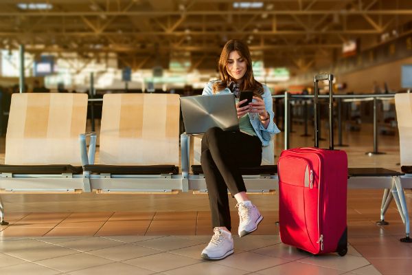 Girl at airport on her phone and laptop