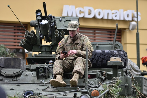 Soldier on armored vehicle checking phone outside McDonalds