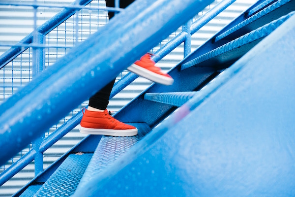 person walking up stairs in red sneakers