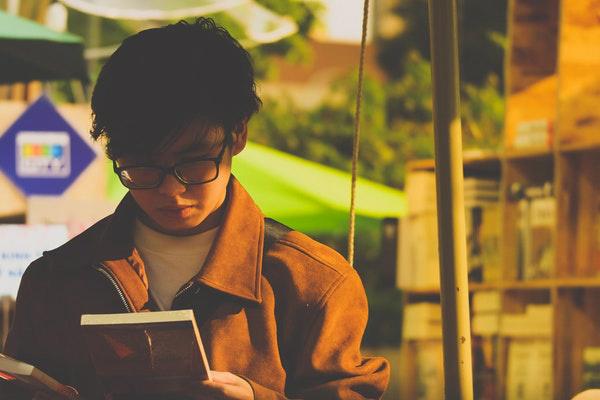 guy picking book